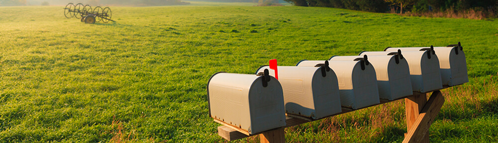 Set of mailboxes with a country scene in the background